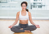 Sporty content brunette sitting in lotus pose