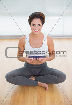 Sporty happy brunette sitting in lotus pose and holding tablet