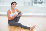 Sporty thoughtful brunette using tablet sitting on the floor