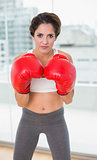 Serious brunette boxing and looking at camera