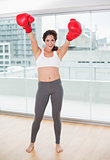Sporty laughing brunette cheering with boxing gloves