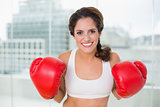 Sporty cheery brunette wearing boxing gloves