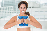 Sporty happy brunette holding dumbbells