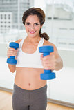 Sporty brunette lifting dumbbells