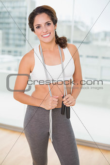 Sporty happy brunette holding skipping rope