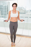Sporty smiling brunette exercising with skipping rope