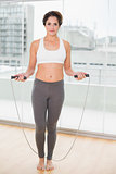 Sporty content brunette exercising with skipping rope