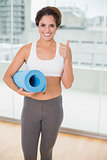 Sporty smiling brunette holding exercising mat