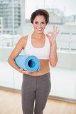 Sporty happy brunette holding exercising mat