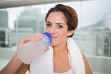 Sporty content brunette holding water bottle