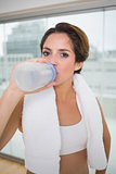 Sporty calm brunette drinking from water bottle