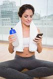 Sporty smiling brunette holding water bottle and smartphone