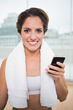 Sporty smiling brunette with towel around neck holding smartphone