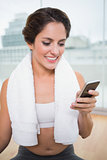 Sporty happy brunette with towel around neck holding smartphone