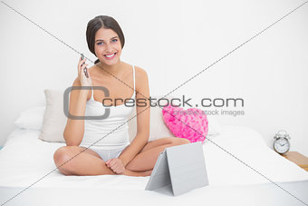 Happy young brown haired model in white pajamas making a phone call