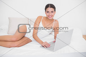 Calm young brown haired model in white pajamas using a laptop