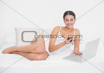 Beautiful young brown haired model in white pajamas using a mobile phone
