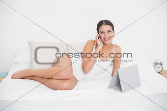 Cute young brown haired model in white pajamas making a phone call
