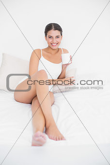 Relaxed young brown haired model in white pajamas drinking coffee