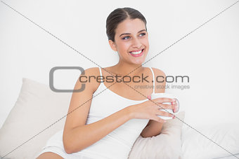 Dreamy young brown haired model in white pajamas drinking coffee