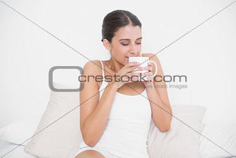 Calm young brown haired model in white pajamas enjoying coffee smell