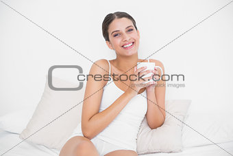 Attractive young brown haired model in white pajamas drinking coffee