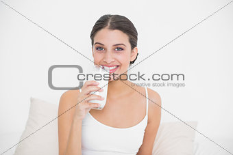 Charming young brown haired model in white pajamas drinking milk