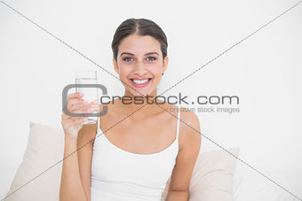 Attractive young brown haired model in white pajamas holding a glass of water