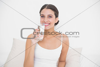 Charming young brown haired model in white pajamas drinking water