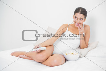 Attentive young brown haired model eating popcorn while watching tv