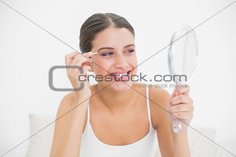 Delighted young brown haired model in white pajamas plucking her eyebrows