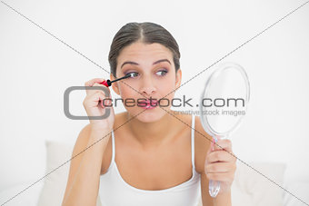 Focused young brown haired model in white pajamas applying mascara