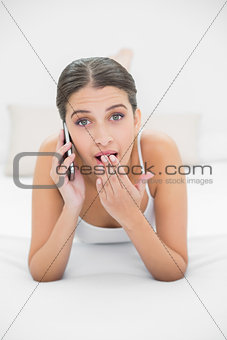Astonished young brown haired model in white pajamas making a phone call
