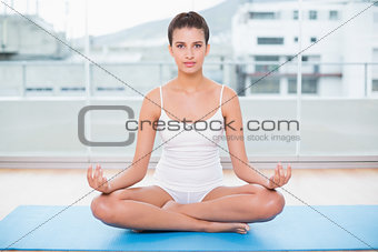 Calm natural brown haired woman in white sportswear practicing yoga