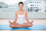 Happy natural brown haired woman in white sportswear practicing yoga