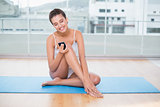 Content natural brown haired woman in white sportswear using her mobile phone