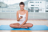 Cheerful natural brown haired woman in white sportswear using her mobile phone