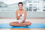 Joyful natural brown haired woman in white sportswear texting with her mobile phone