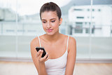 Pensive natural brown haired woman in white sportswear texting with her mobile phone