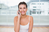 Content natural brown haired woman in white sportswear making a phone call