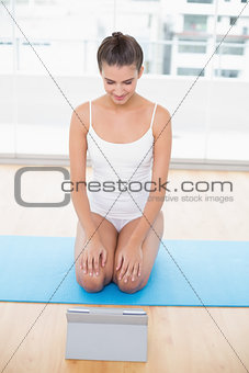 Attentive natural brown haired woman in white sportswear looking at a tablet pc
