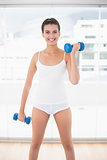 Content natural brown haired woman in white sportswear lifting dumbbells