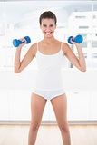 Happy natural brown haired woman in white sportswear exercising with dumbbells