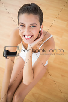 Beautiful natural brown haired woman in white sportswear adusting her earphones
