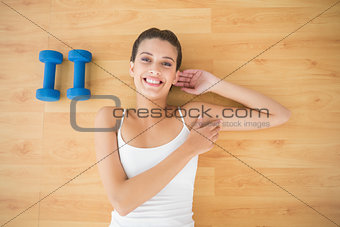 Content natural brown haired woman in white sportswear lying on the floor