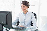 Smiling classy brown haired businesswoman using a computer