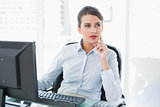 Thoughtful classy brown haired businesswoman using a computer