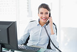 Cheerful classy brown haired businesswoman answering the telephone