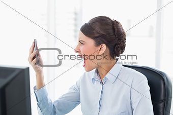 Angry classy brown haired businesswoman shouting at her mobile phone