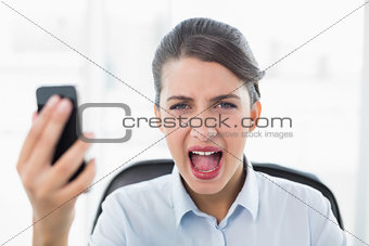 Annoyed classy brown haired businesswoman screaming while holding a mobile phone
